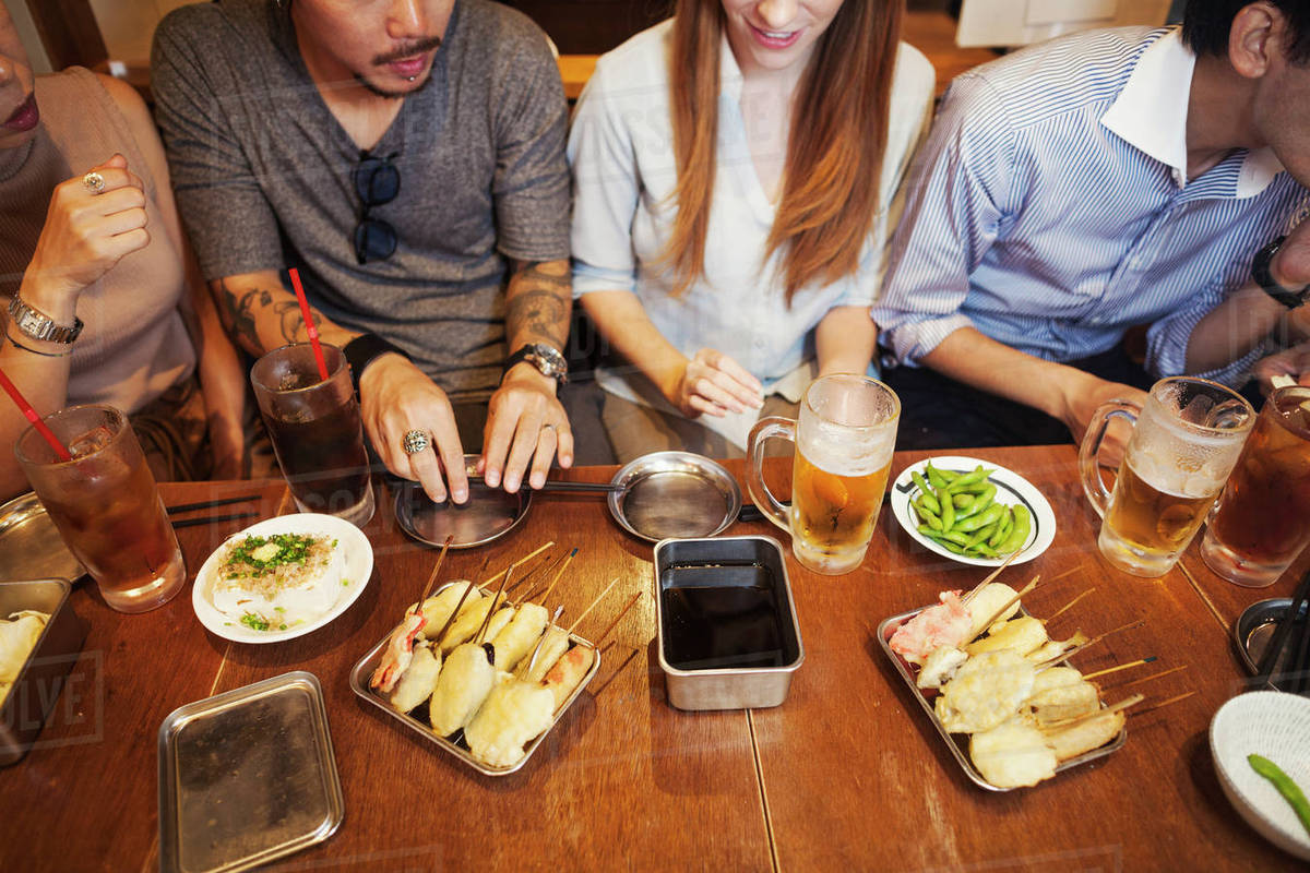 High Angle View Of Five People Sitting Sidy By Side At A Restaurant Table With Food And Drink Stock Photo