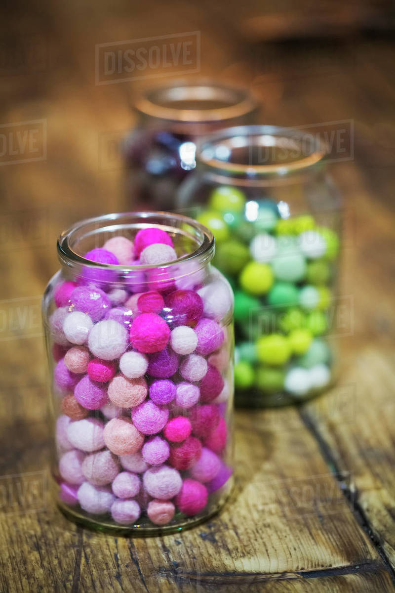 Close Up Of Glass Jars With Colourful Small Fabric Balls On Wooden Table Stock Photo Dissolve
