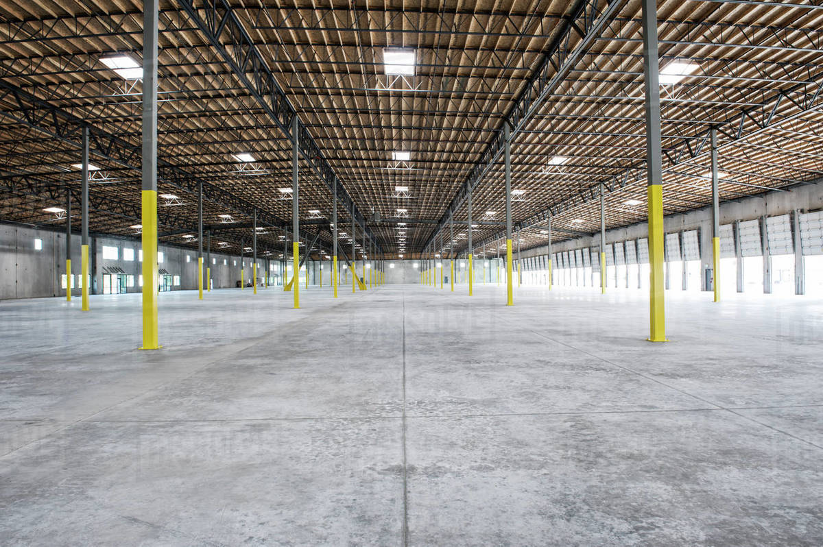 Wide angle interior view of large empty warehouse and loading dock doors -  Stock Photo - Dissolve