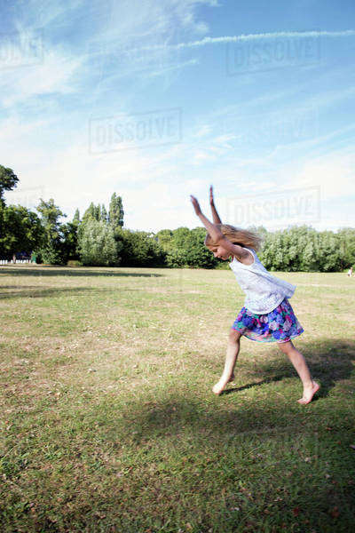 Young girl playing in a park, preparing to do a handstand.  Royalty-free stock photo