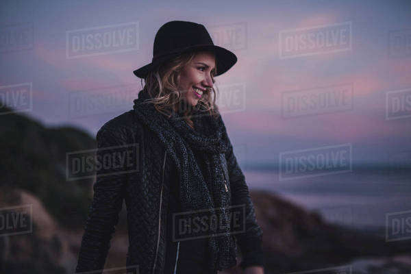 Portrait of a woman smiling on a coast at sunset Royalty-free stock photo
