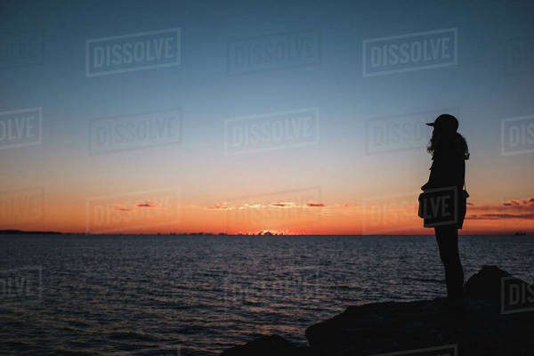 Woman watching the sunset by the sea Royalty-free stock photo
