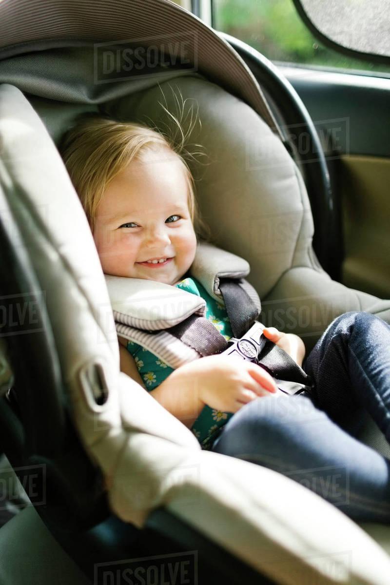 Baby Girl Sitting In Car Seat During Trip
