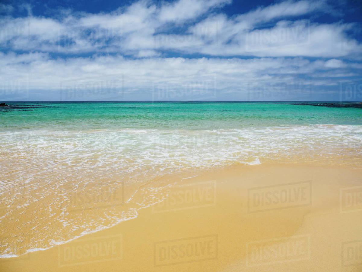 aa0cd6d1e53ed White clouds above sea and sandy beach - Stock Photo - Dissolve