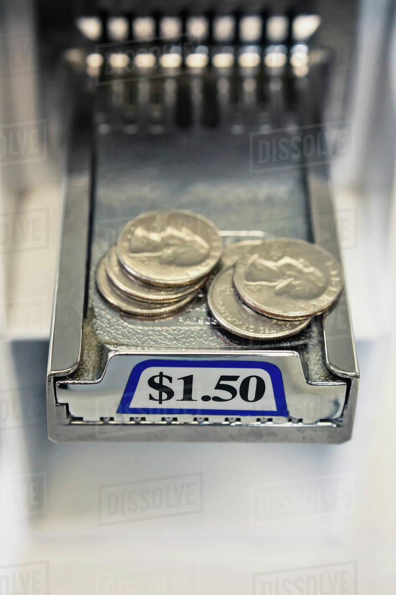 Quarters on sliding tray of coin operated washing machine stock photo