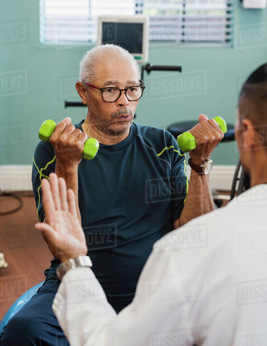 Senior man exercising with therapist during physical therapy Royalty-free stock photo