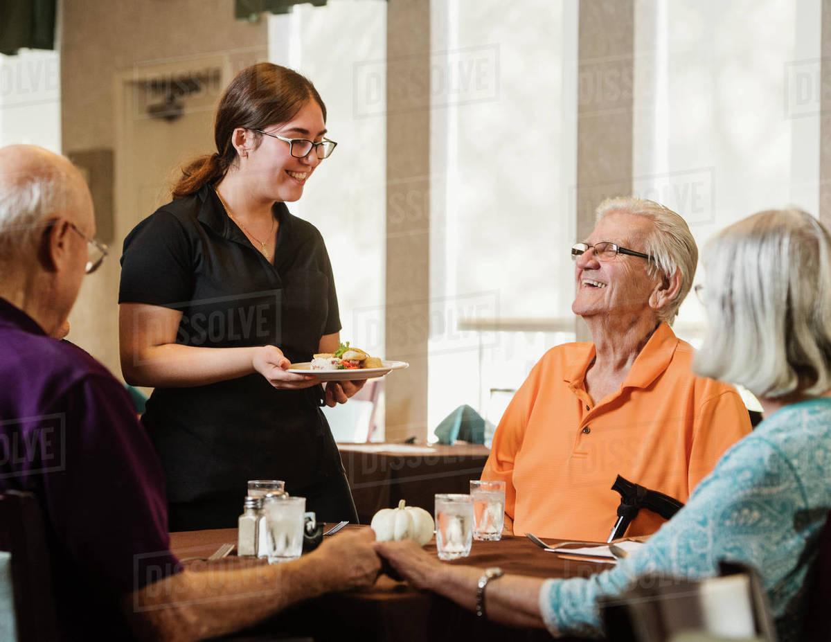 Waitress bringing meal to senior people at table Royalty-free stock photo