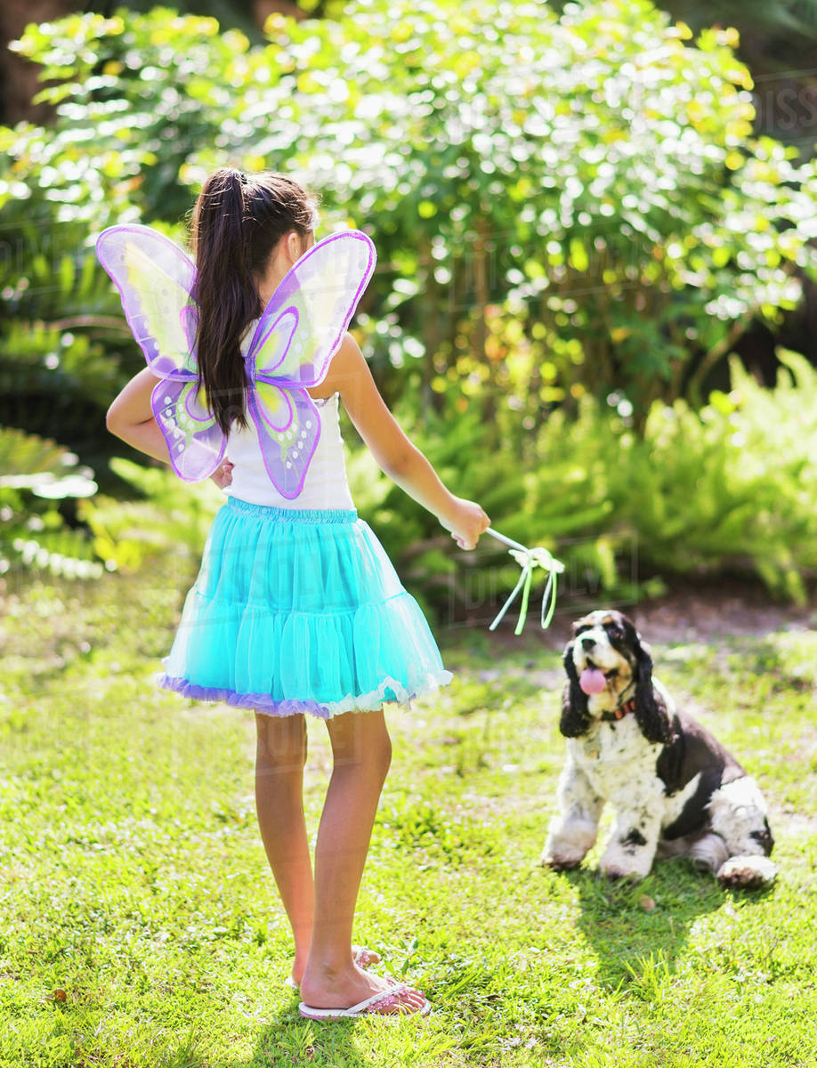 Girl (8-9) wearing fairy costume playing with dog Royalty-free stock photo