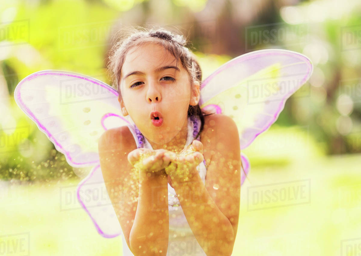 Girl (8-9) blowing fairy dust Royalty-free stock photo