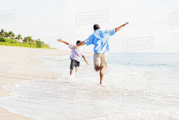 Father and son (10-11) running on beach Royalty-free stock photo