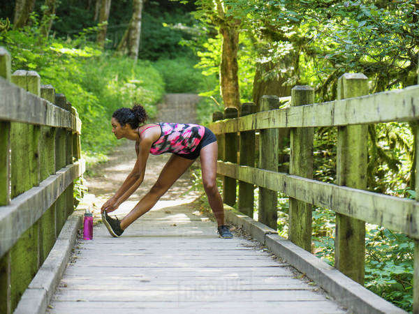 Young women stretching on footbridge Royalty-free stock photo