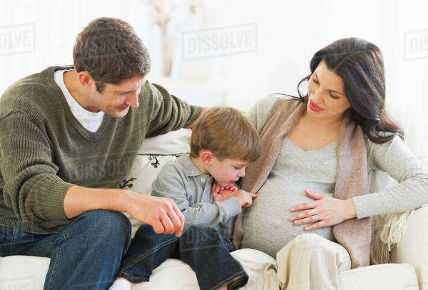 Boy (4-5) touching pregnant mother's belly Royalty-free stock photo