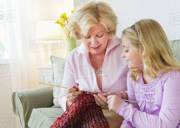 Grandmother with granddaughter (8-9) knitting at sofa Royalty-free stock photo