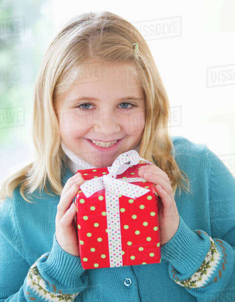 Portrait of smiling girl (8-9) holding gift Royalty-free stock photo