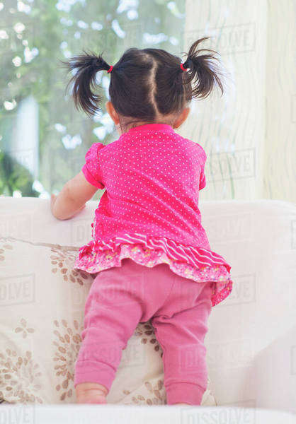 Baby girl (12-17 months) looking through window Royalty-free stock photo