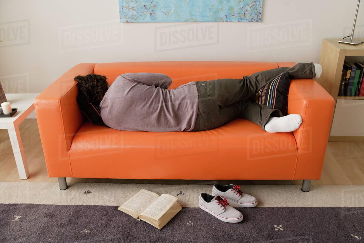 Man sleeping on sofa   Stock Photo   Dissolve
