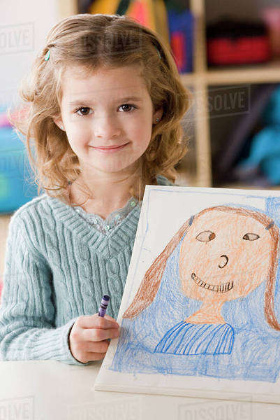 Portrait of smiling girl (6-7) showing her drawing Royalty-free stock photo