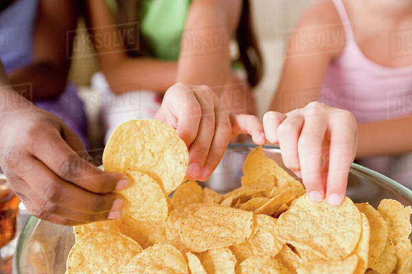 Three girls (10-11) reaching for crisps Royalty-free stock photo