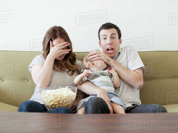 Young couple with baby boy (6-11 months) watching horror film  Royalty-free stock photo
