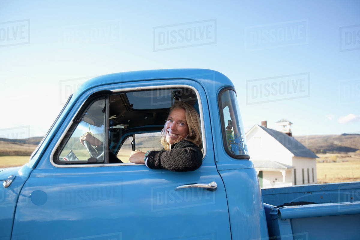 USA, Colorado, Carbondale, Cowgirl driving old fashioned pickup ...