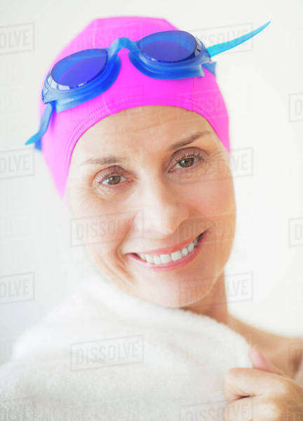 Portrait of smiling woman in swimming cap and goggles Royalty-free stock photo