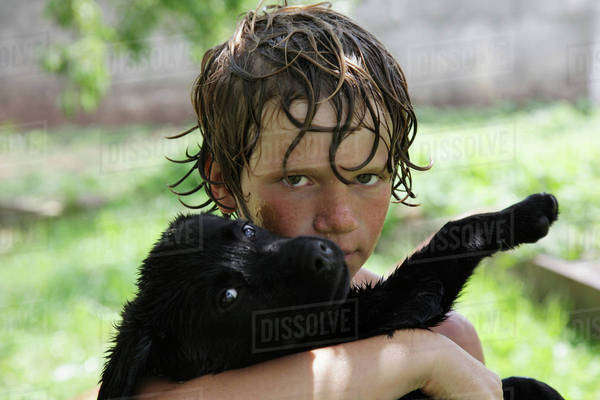 Portrait of wet Boy (10-11) with Labrador puppy  Royalty-free stock photo