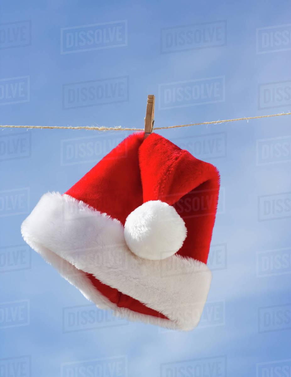 91c6705f670 Santa Claus hat hanging on clothesline - Stock Photo - Dissolve
