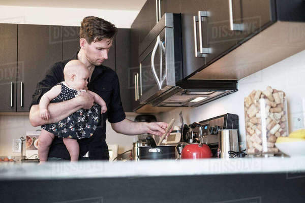 Father holding baby daughter (2-5 months) while stirring food Royalty-free stock photo