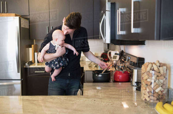 Father kissing baby daughter (2-5 months) while stirring food Royalty-free stock photo