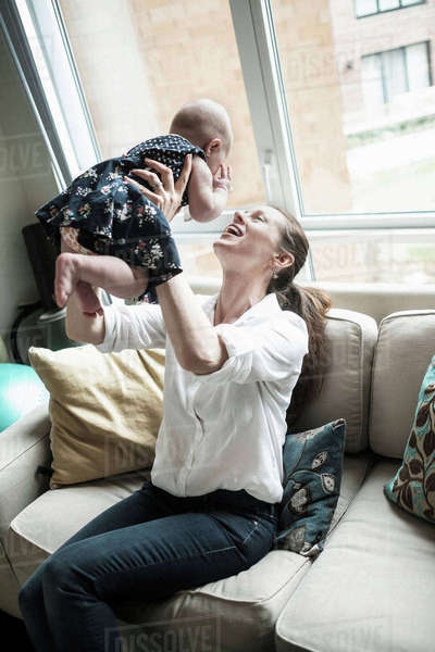 Mother playing with baby daughter (2-5 months) in living room Royalty-free stock photo