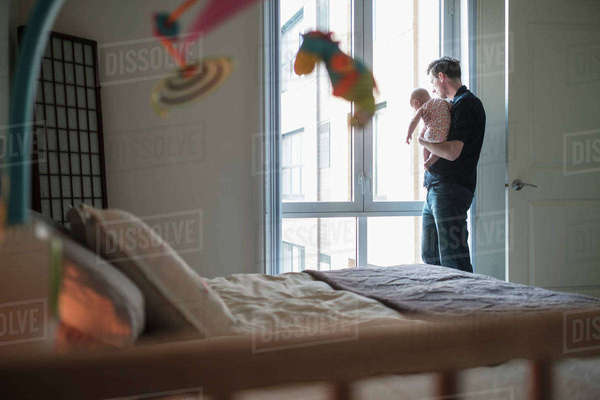Father looking through window with daughter (2-5 months) Royalty-free stock photo