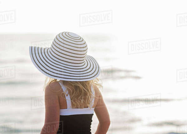 Girl (4-5) in striped sunhat by sea Royalty-free stock photo