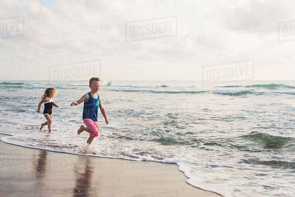 Boy (6-7) and girl (4-5) running on beach by water Royalty-free stock photo