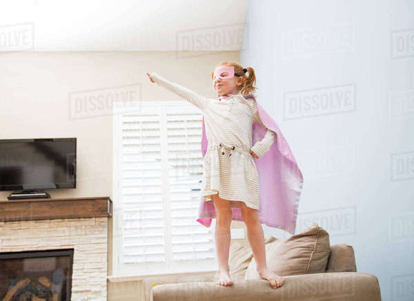 Little girl (4-5) playing superman on sofa Royalty-free stock photo