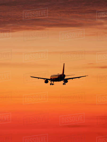 Airplane against orange sky Royalty-free stock photo