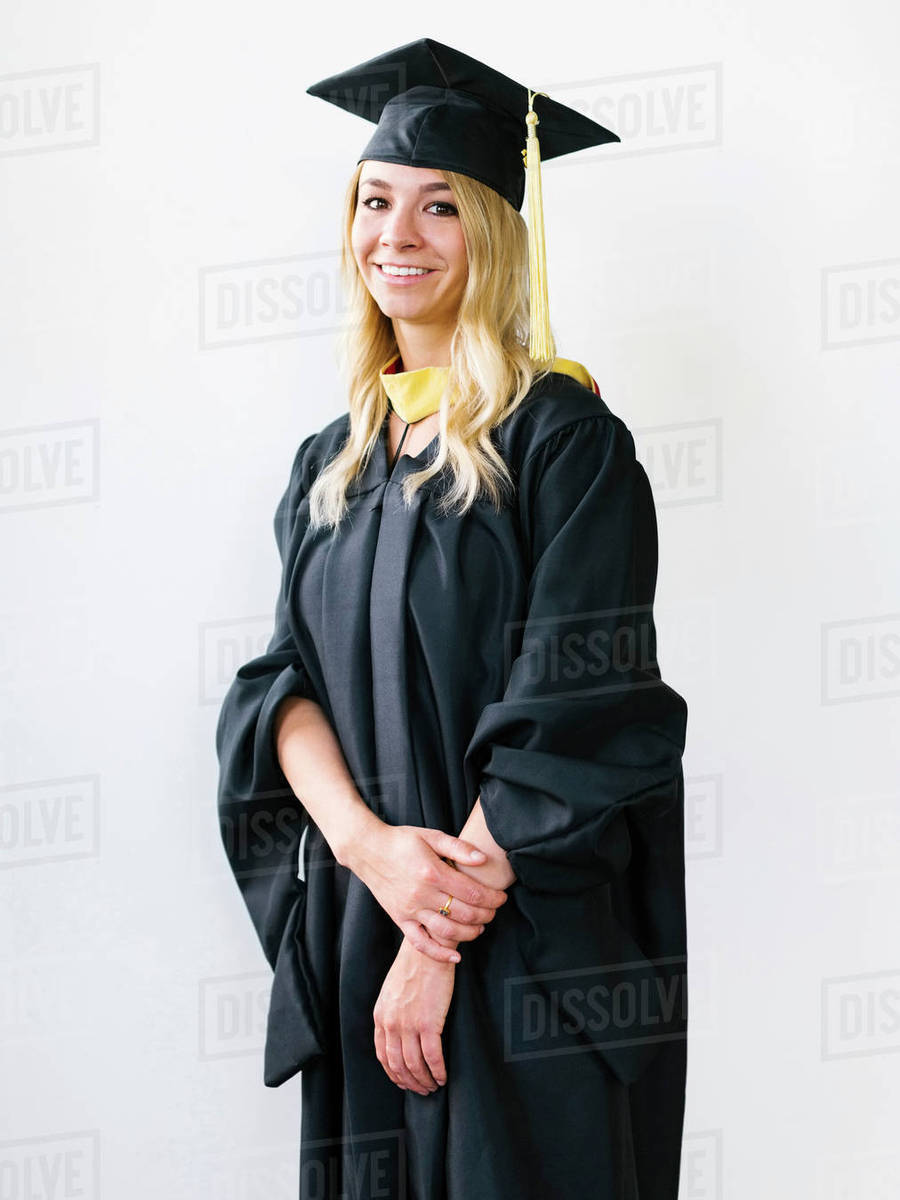 Portrait of young blond woman wearing graduation gown - Stock Photo ...