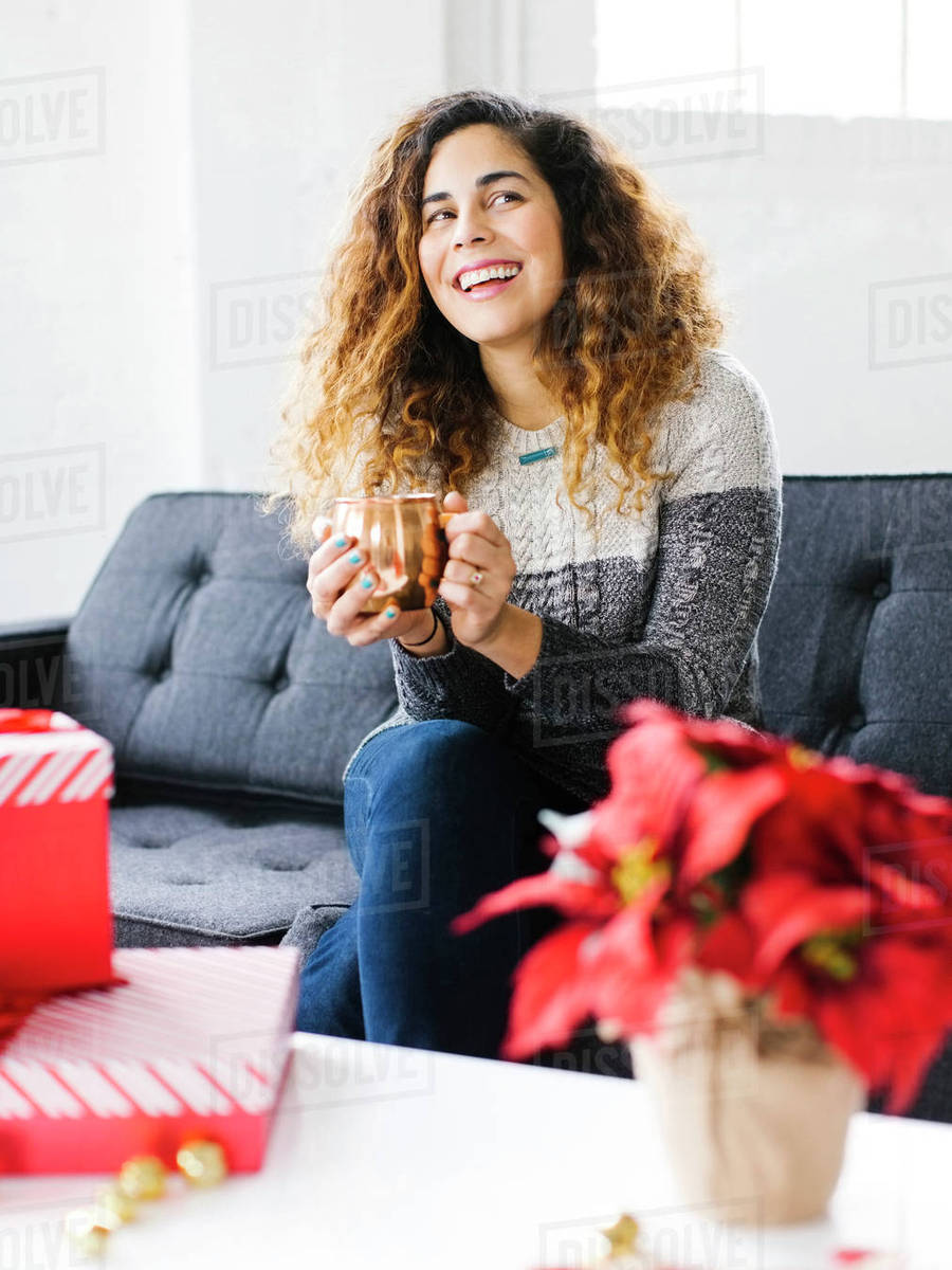 Happy woman on sofa, holding mug with Christmas gifts in foreground ...