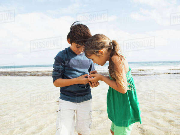 Portrait of girl (6-7) and boy (10-11) on beach Royalty-free stock photo
