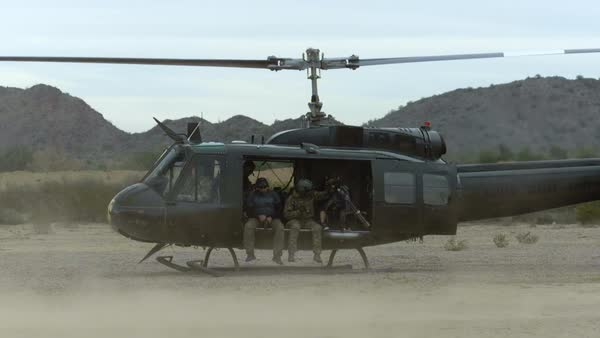 Huey helicopter taking off, with riders, the desert Royalty-free stock video