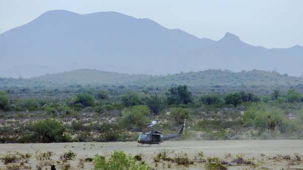 Huey helicopter taking off in the desert, wide shot. Royalty-free stock video
