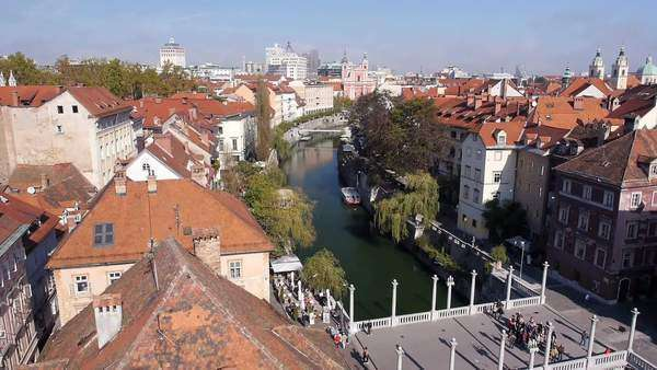 Aerial - Medieval houses near the river with bridge. Birds flying by Royalty-free stock video
