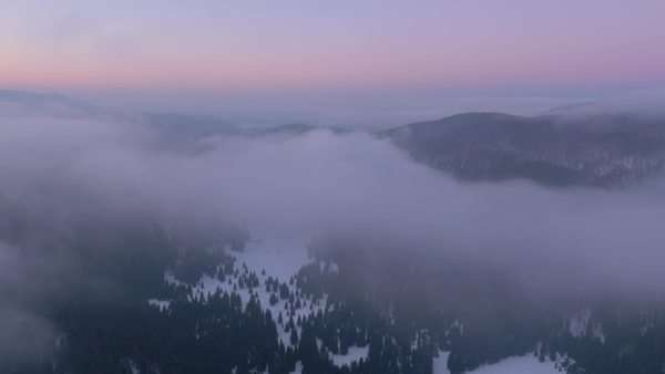 Aerial - Above the cloudy winter valley at sunset Royalty-free stock video