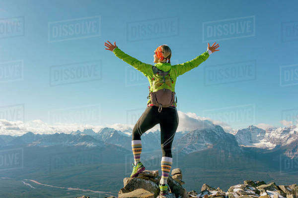 Trail runner stands on mountain summit, arms out. Royalty-free stock photo