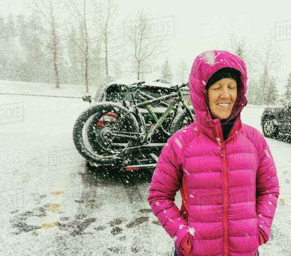 Smiling woman stands beside a car loaded with bikes in a snowstorm. Royalty-free stock photo