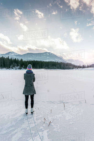 Woman on figure skates looks out over frozen pond, in mountains. Royalty-free stock photo