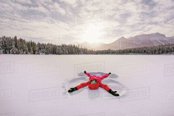 Woman makes a snow angel on a snow covered lake, in mountains. Royalty-free stock photo