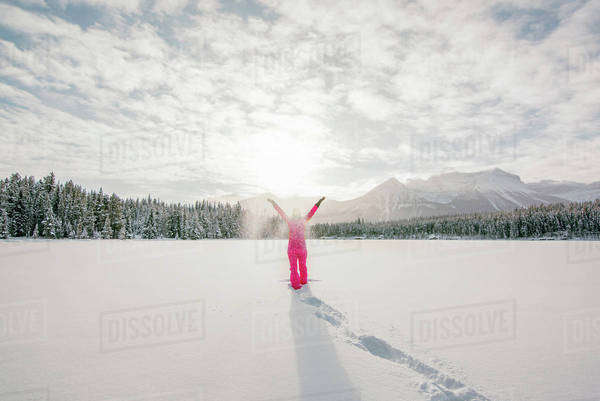 Woman throws snow up in the air while standing on a snowy, frozen mountain lake. Royalty-free stock photo