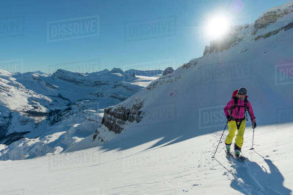 Female backcountry skier reaching the top of a col on a sunny day. Royalty-free stock photo