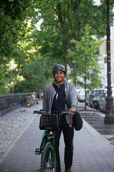 Portrait of happy man with bicycle standing on footpath in city Royalty-free stock photo