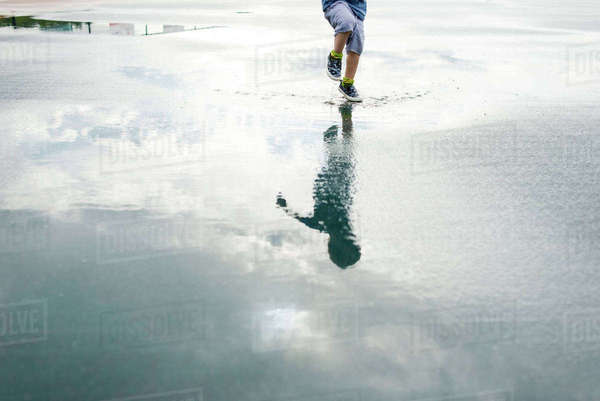 Reflection of boy jumping in puddle Royalty-free stock photo